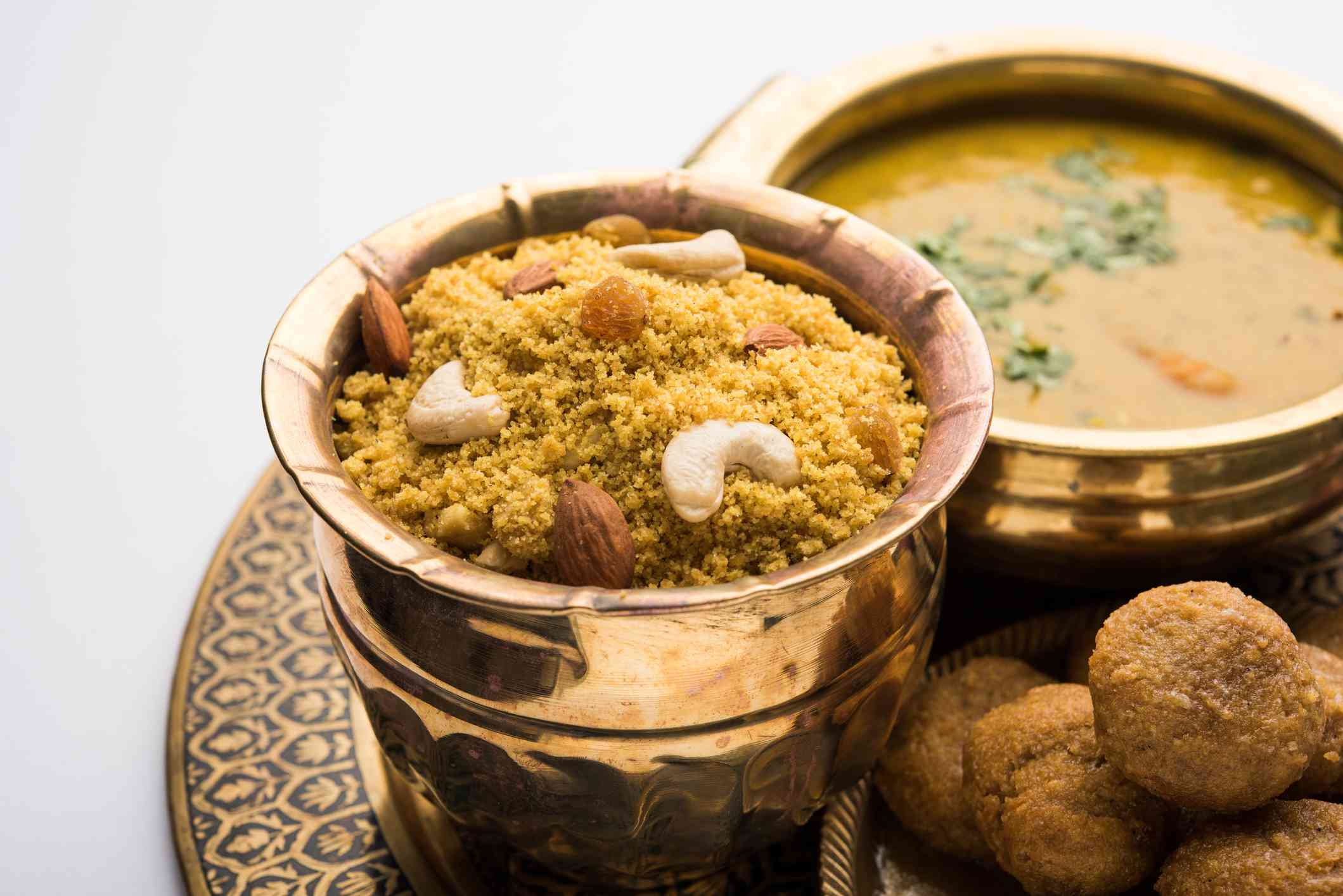 plate of dal bathi churma with golden plates and bowls