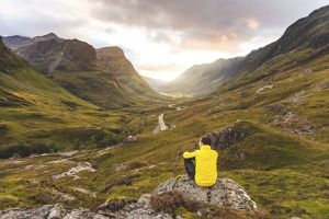 A man in a yellow jacket sits on a rock looking down a mountain valley with a road running through it.