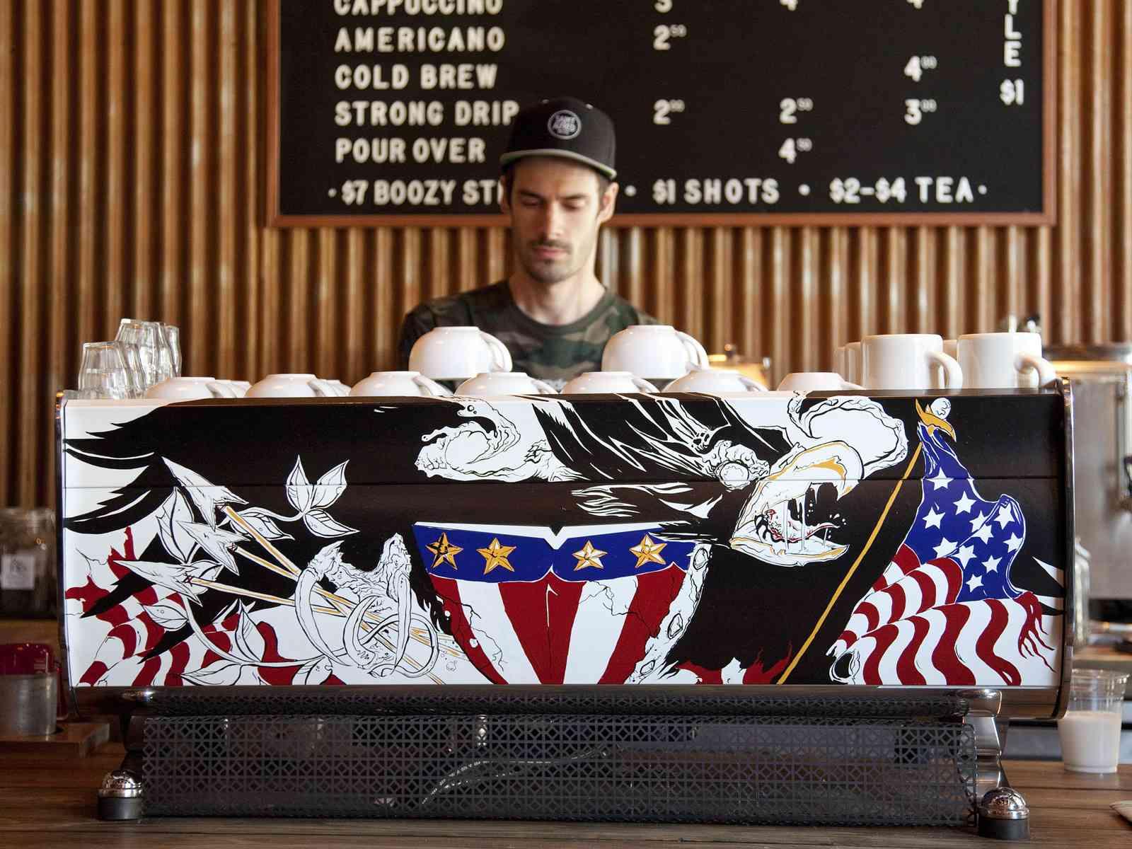 Decorate espresso machine with a male barista behind it