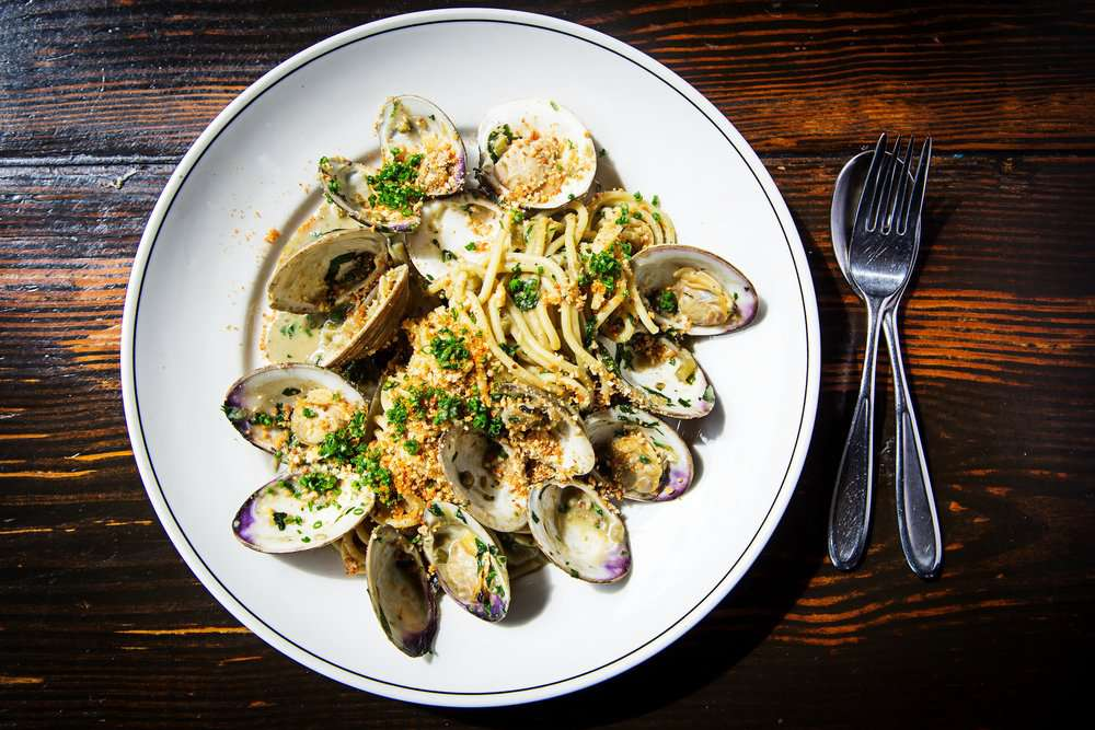 Overhead shot of a plate of clams and spaghetti on a dark wooden table. There is a fork resting on top of a spoon to the right of the plate