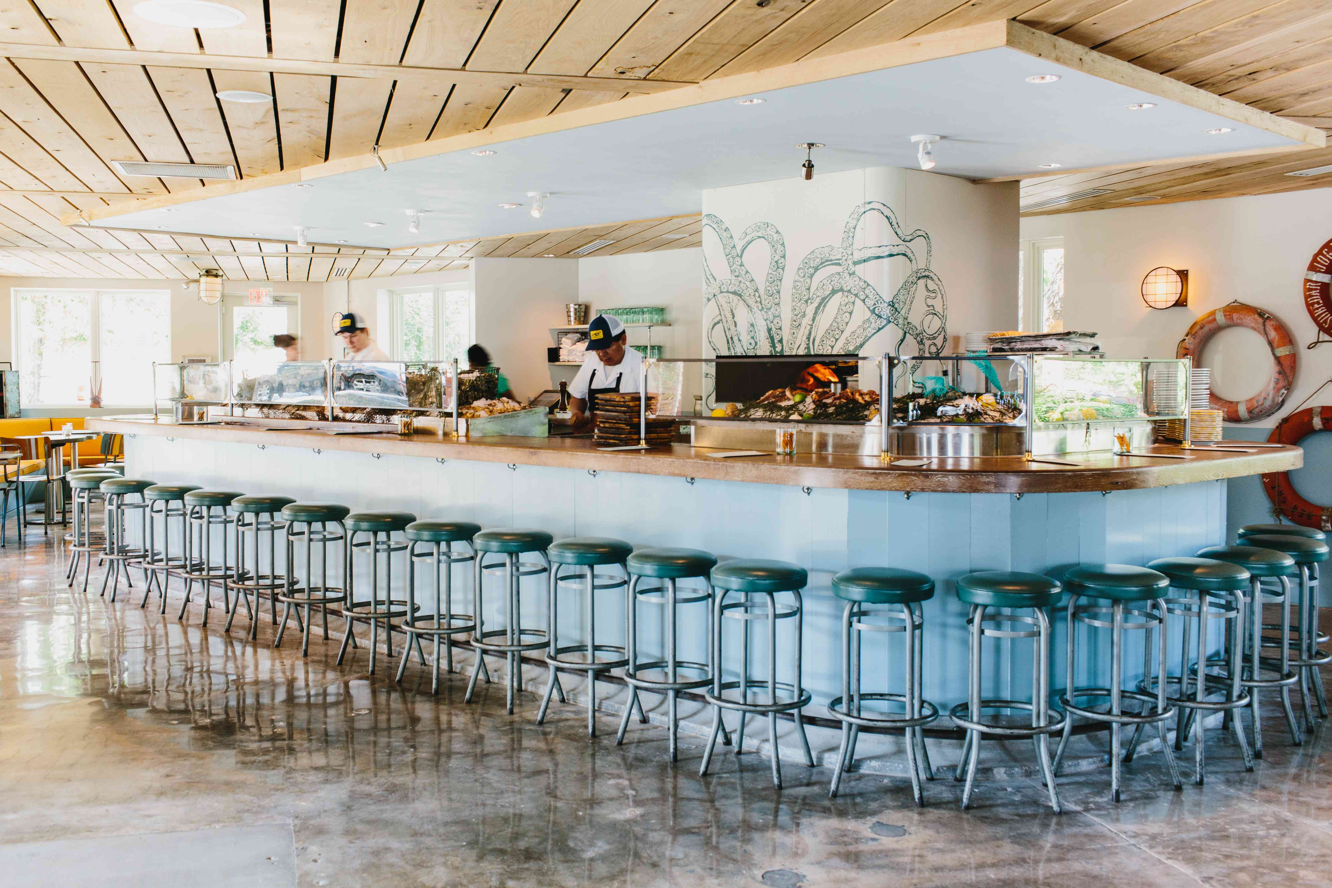 metal-legged stools with teal seat lined up around a long bar with three people behind it