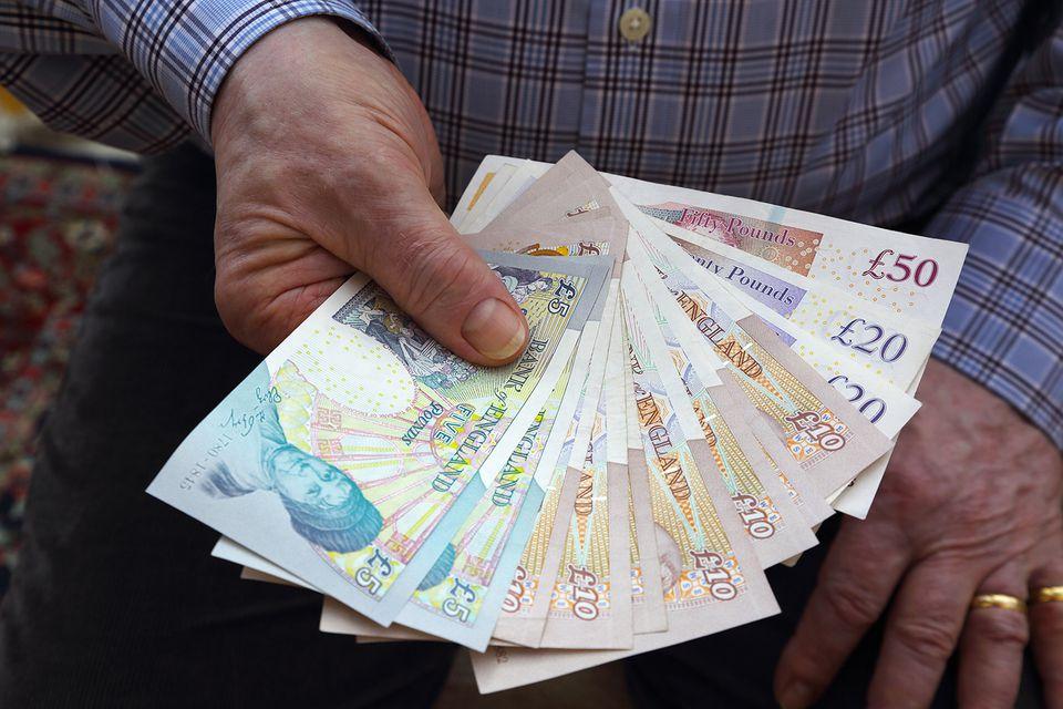 Pensionista con billetes de banco británico en la mano derecha