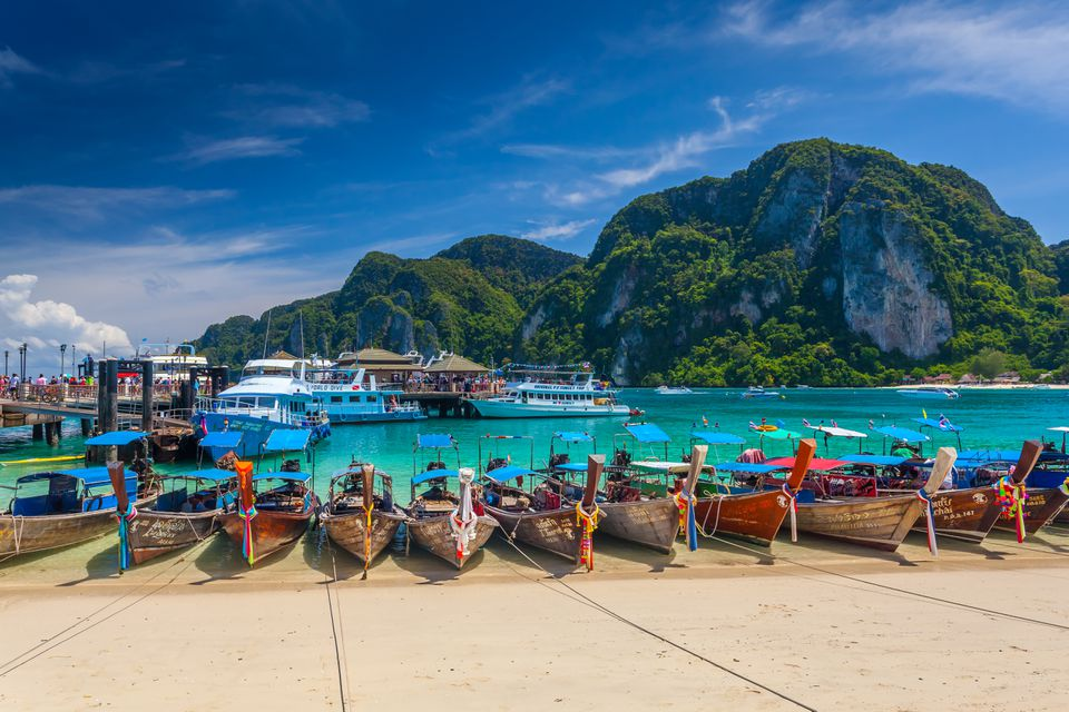 Beach in Thailand during high season lined with boats