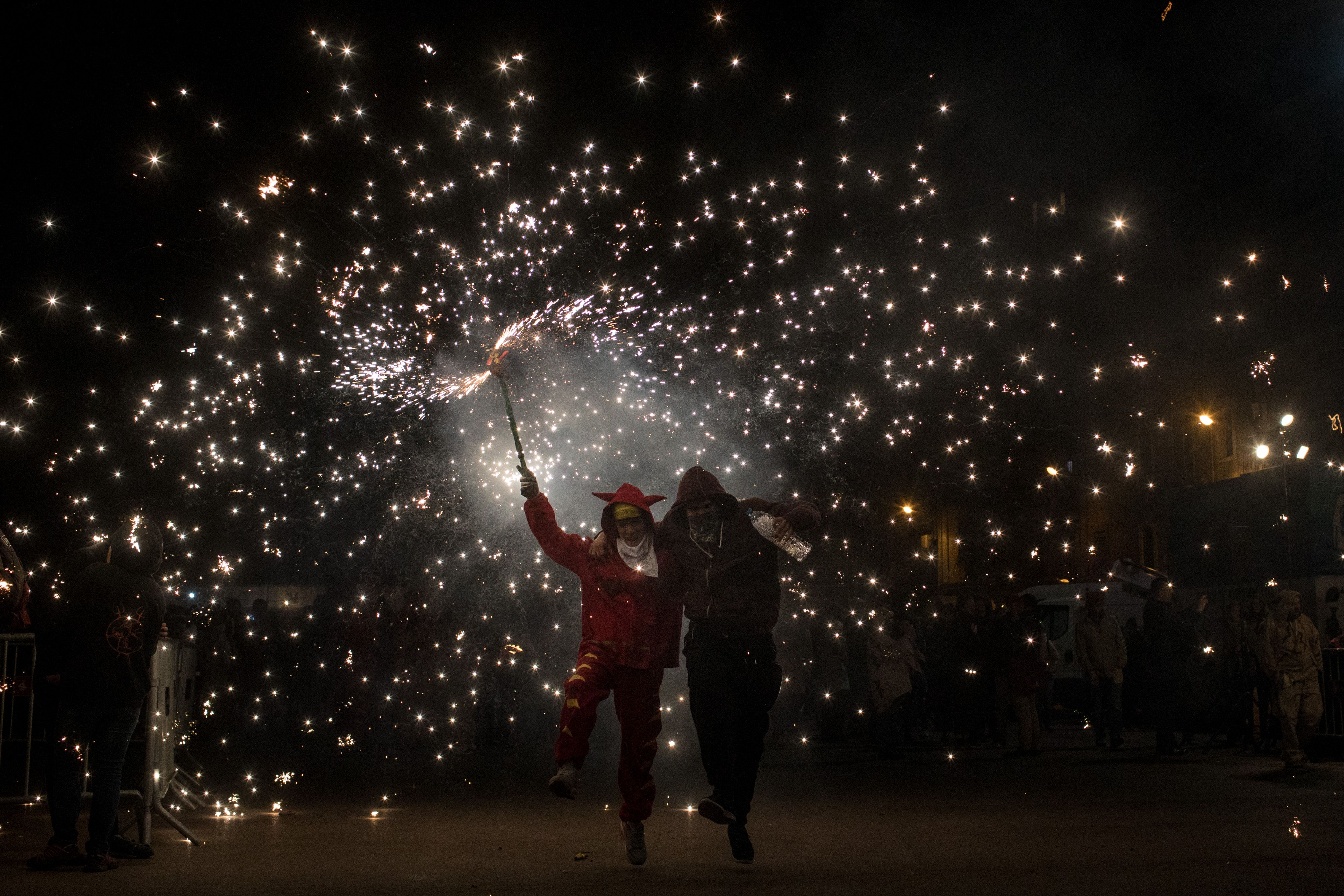 Two kids playing with sparklers on the Day of Innocents in Barcelona