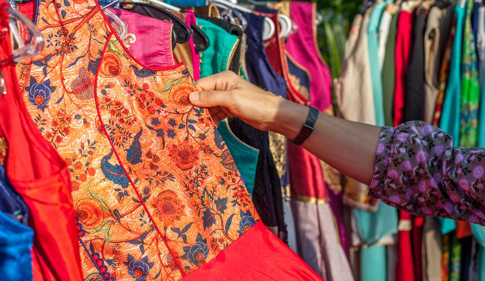 Cropped Image Of Hand Choosing Dress At Market
