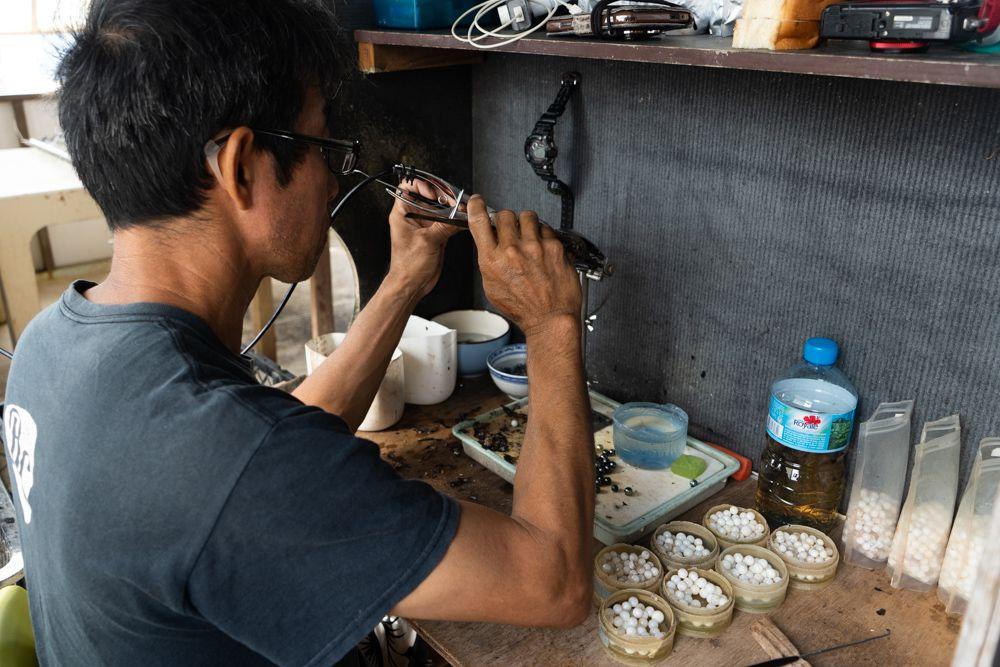 A man inspecting pearls at a Pearl Farm