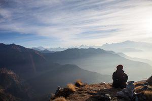 A tourist admires the Himalayan sunrise in Chopta, Uttarakhand, India