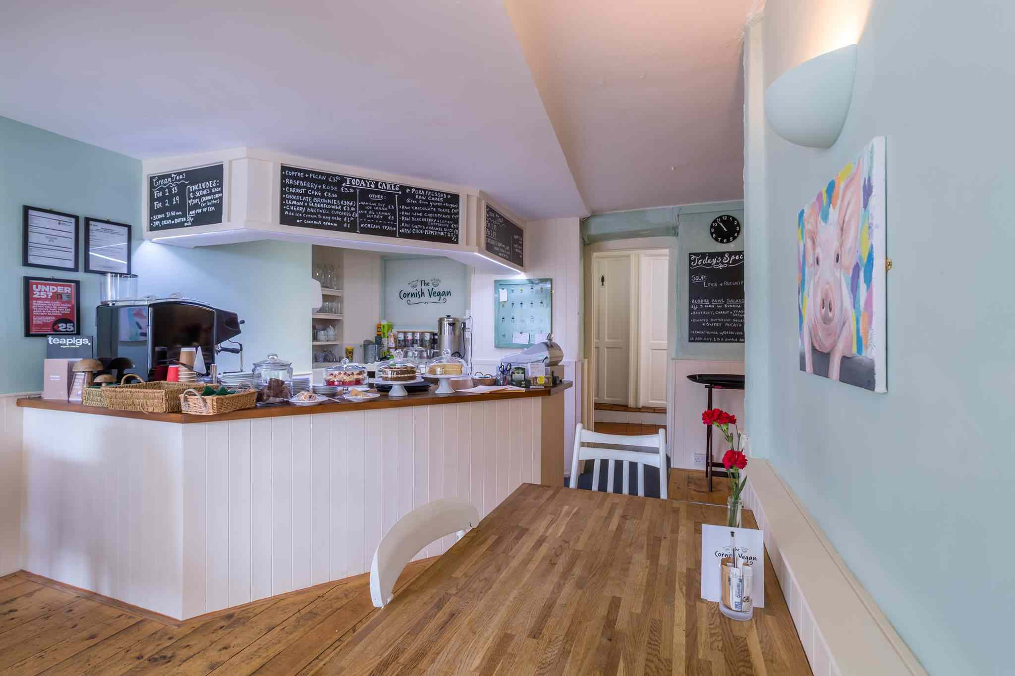 White and pastel blue interior of The Cornish Vegan restaurant. There is a cafe counter and small wooden table