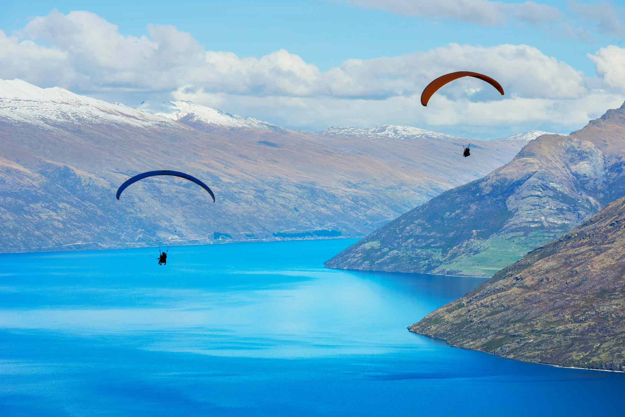 two paragliders with blue lake and snowy mountains in background