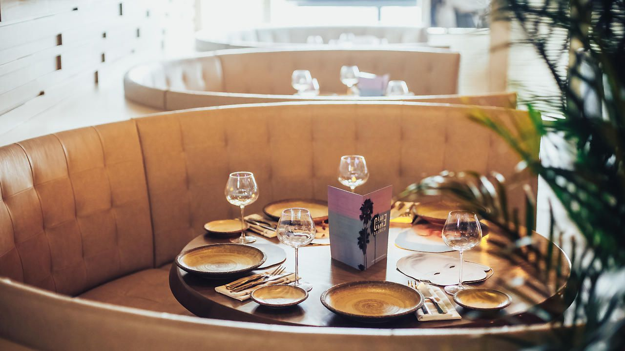 round booth with tan leather upholstery and a tablw with four place settings. there is an out of focus palm plant in the foreground on the right side of the image