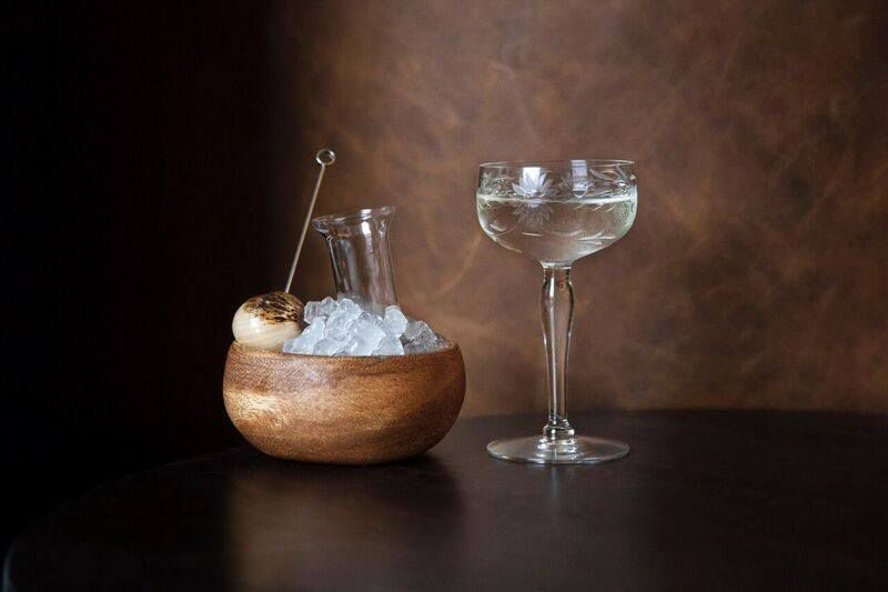 A Gibson cocktail with the skwered onion and a glass bottle of brine in an ice filled bowl separate from the alcohol