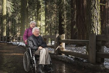 Senior woman pushing man in wheelchair through forest at Sequoia National Park, California, USA
