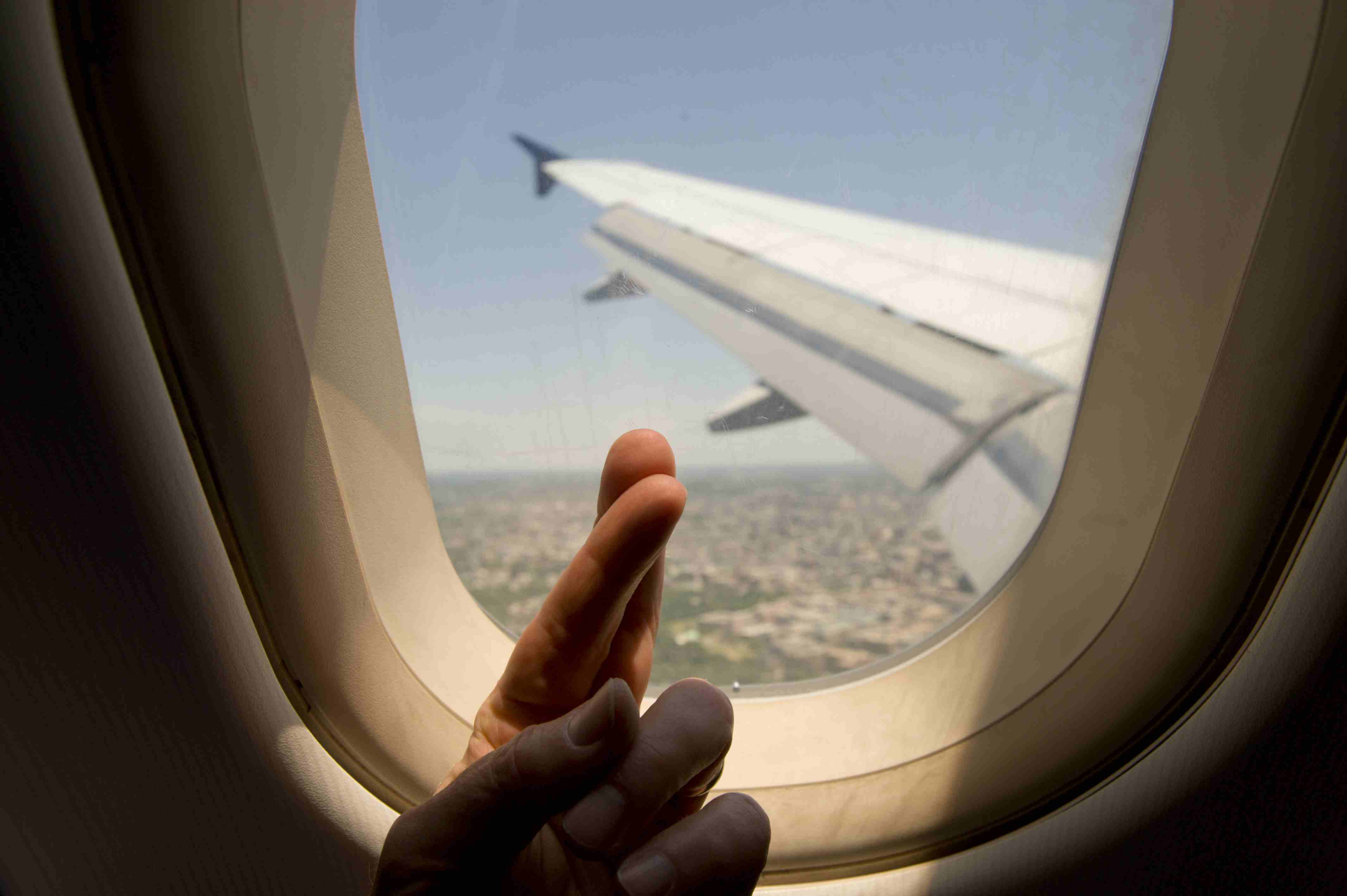 Male passenger crossing fingers while looking out an airplane window