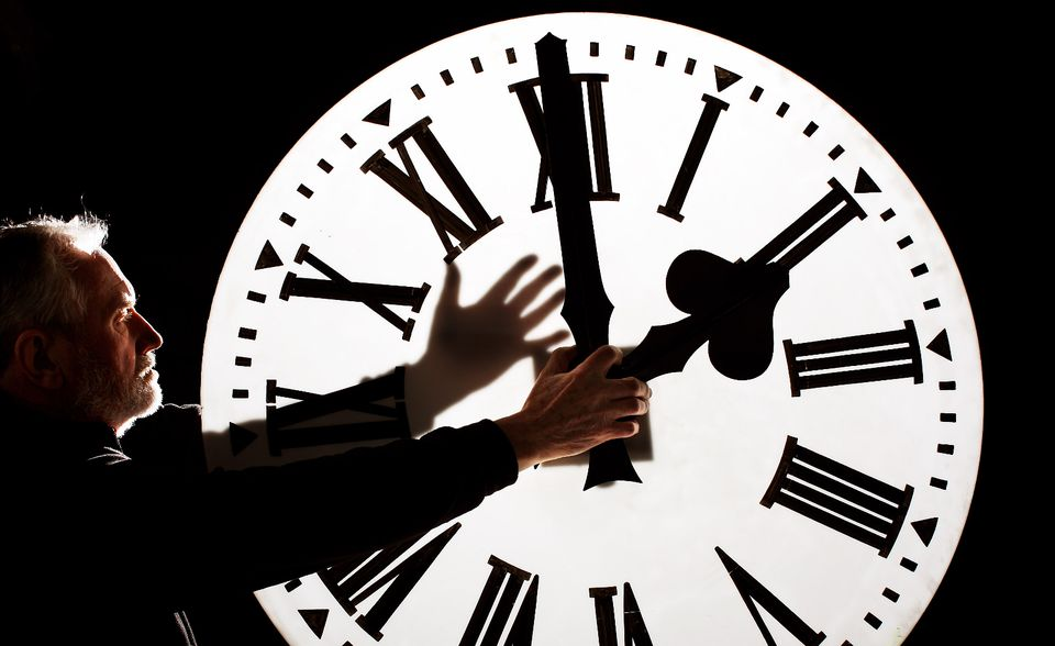 Man moving back the hour hand on a large clock.