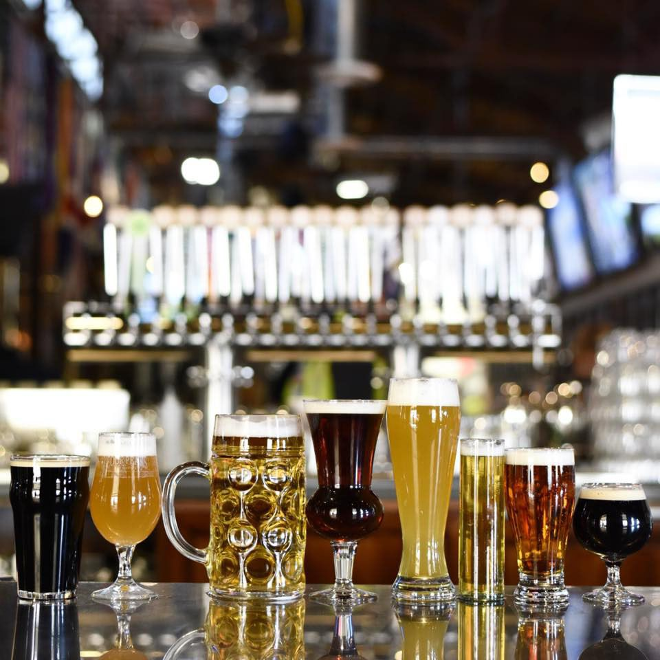 A line of glasses of beers. All the glasses are different shapes accenting each beer. The blurred background is of the bar