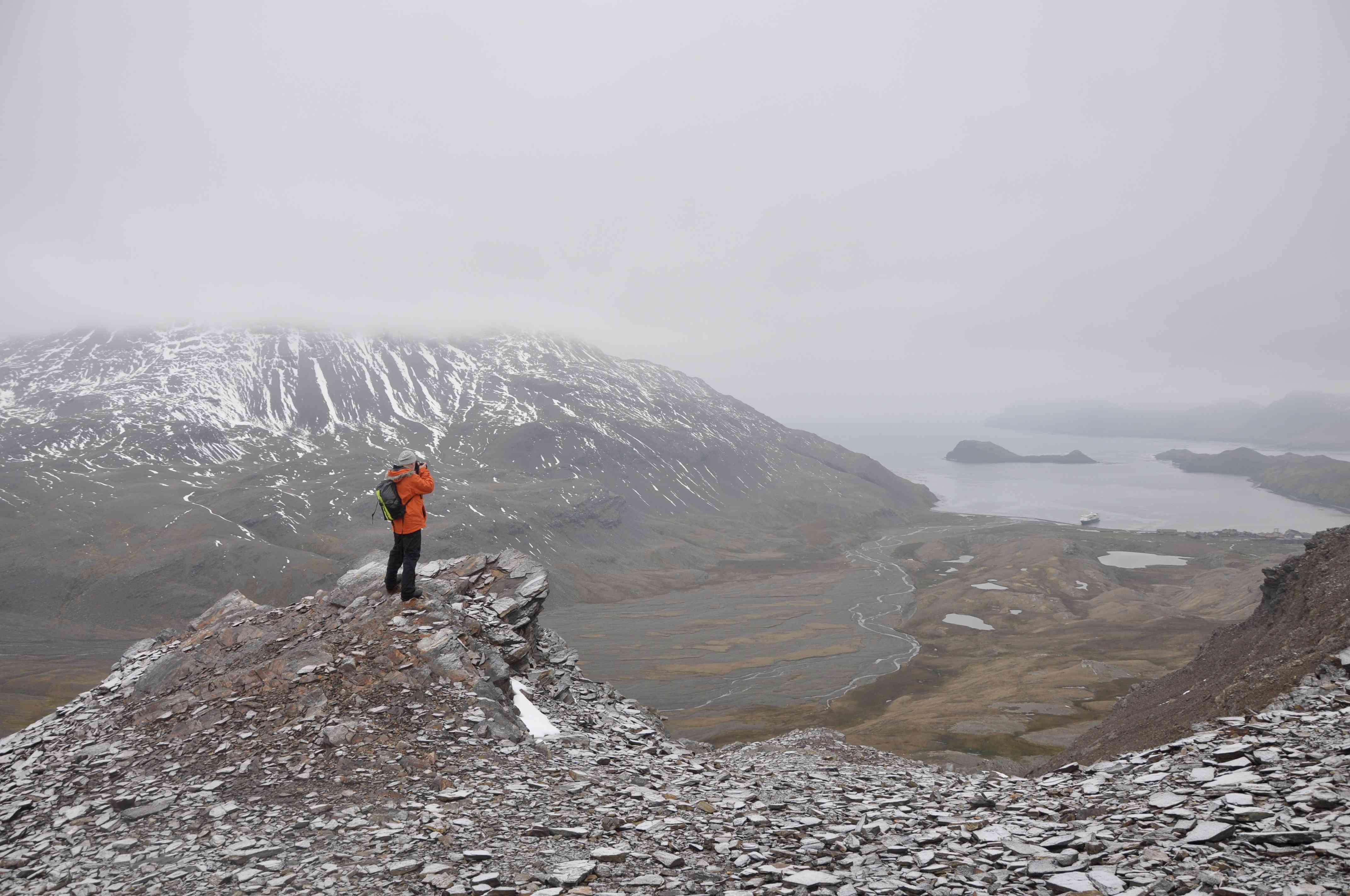 Un fotógrafo se para en un acantilado tomando una foto en el valle de una montaña