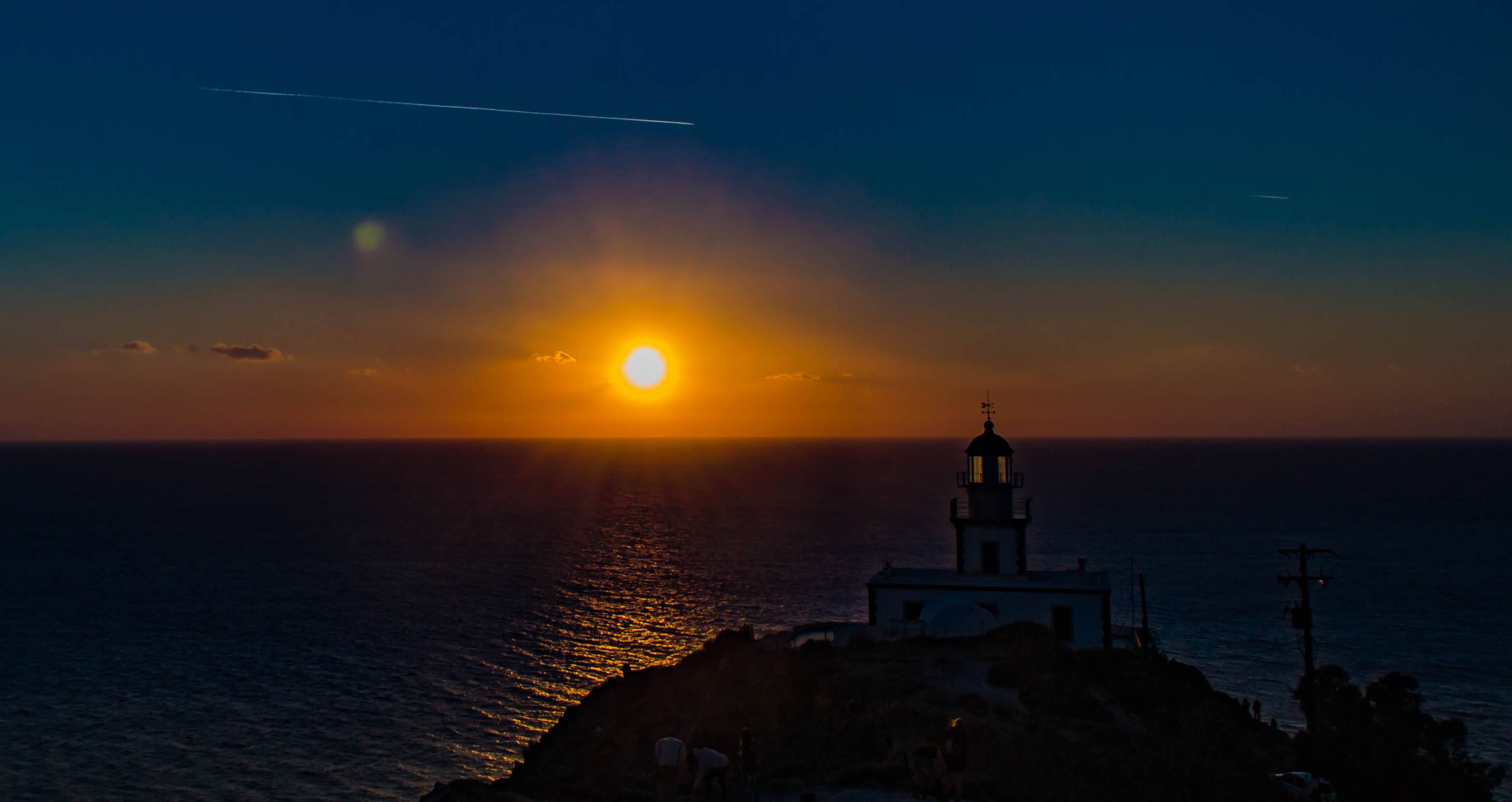 Lighthouse On Mountain By Sea Against Sky During Sunset At Santorini