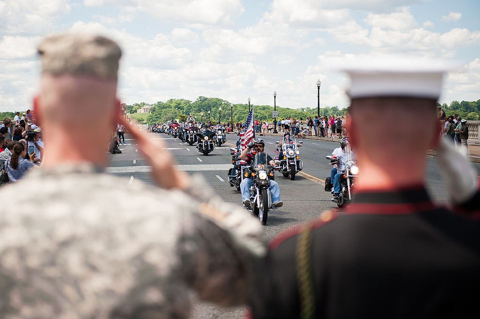 Military veterans exchange salutes with Rolling Thunder riders