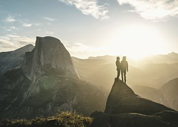 Two people stand on a cliff looking out at Half Dome in Yosemite National Park