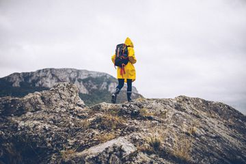 Young woman in a yellow raincoat, hiking through the nature, enjoying the clean air.