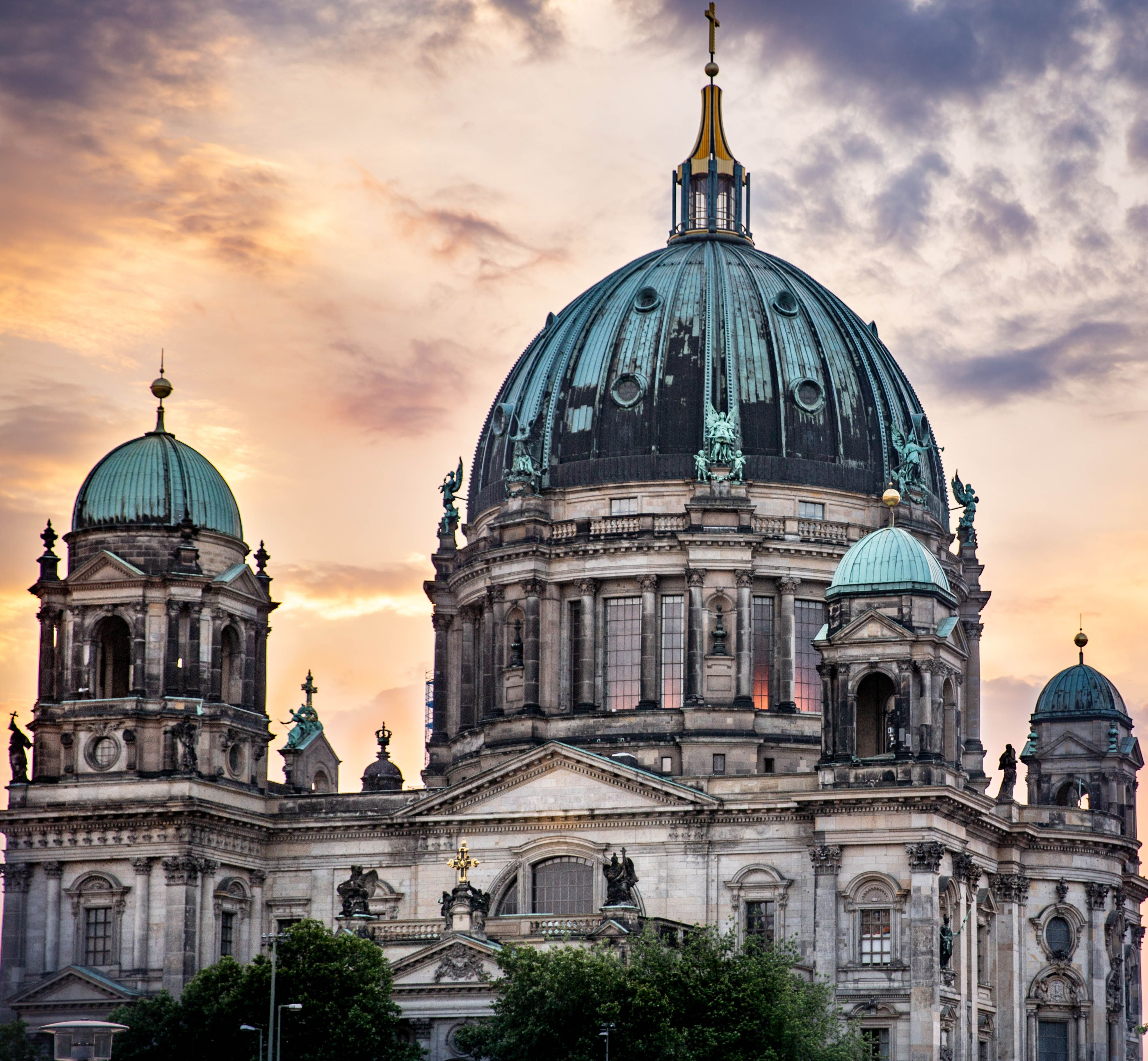 The top of Berlin Cathedral with the sun setting behind it.