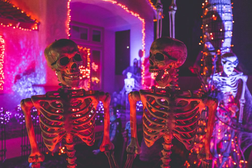 Two skeletons lit in a red light outside of a house that is decorated for halloween