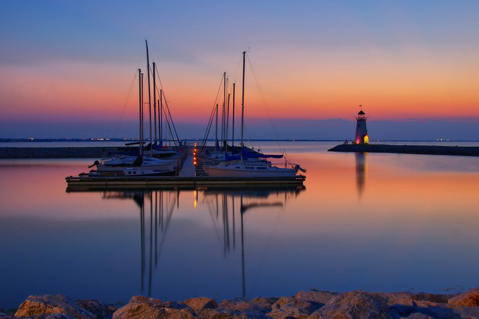 View of lake Hefner with boats at sunset light house in background, Oklahoma City