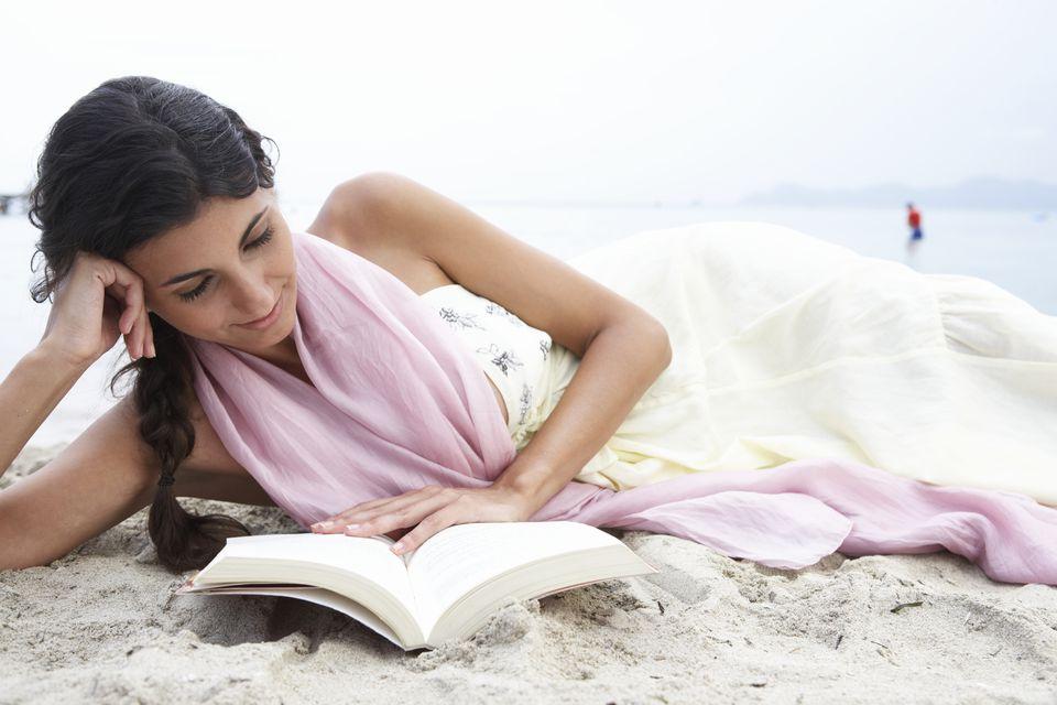 mujer joven leyendo en la playa