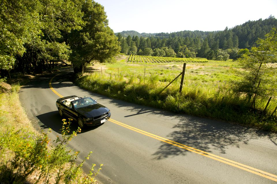 Couple driving convertible, Napa Valley, California