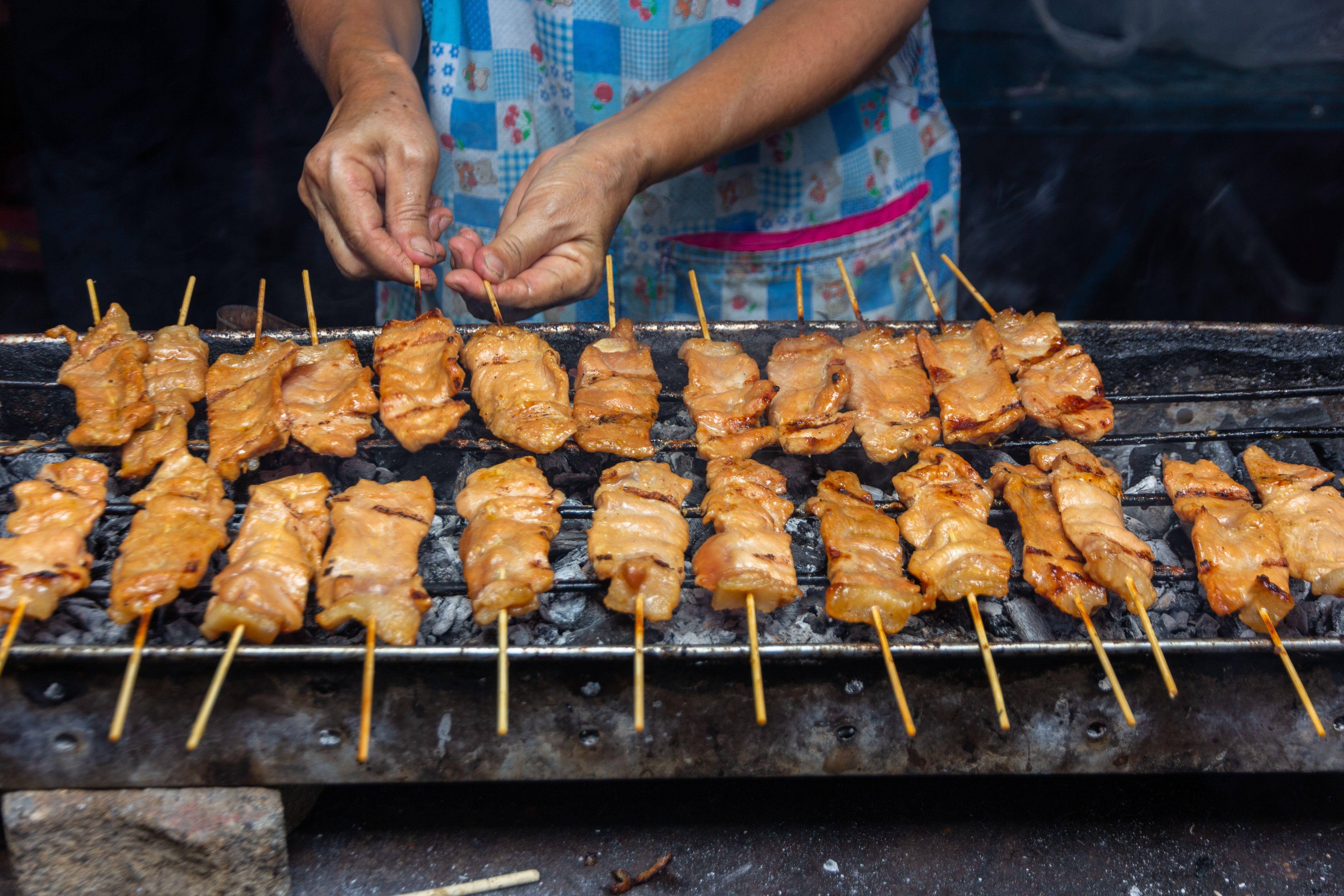 Vendor grilling moo ping (pork skewers) in Thailand