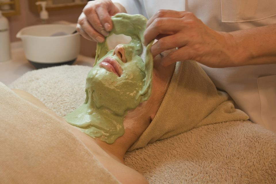 Aesthetician peeling off a seaweed mask