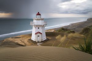 white lighthouse on sandy dunes with a long bay and sea in the background