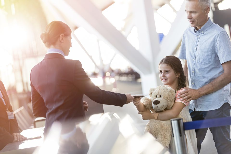 Flight attendant checking ticket of girl with teddy bear in airport