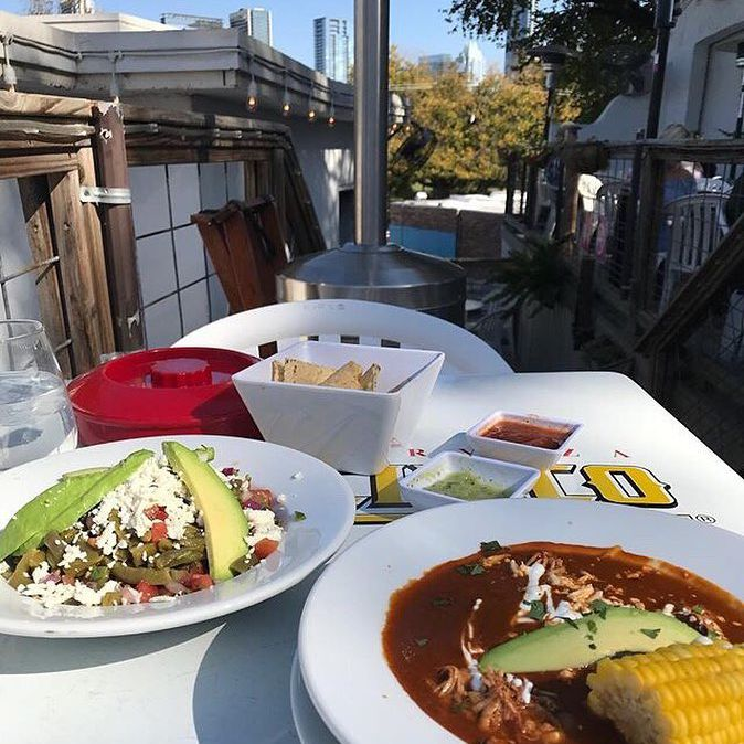 Two dishes on an outdoor patio at El Alma in Austin, Texas