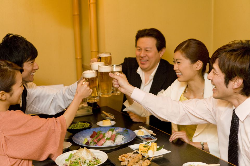 People giving a cheers in Japanese with beers