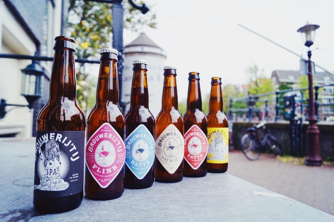 6 botellas de cerveza seguidas en una repisa exterior. Tres botellas tienen las tapas puestas