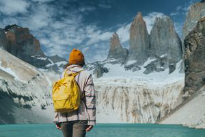 Woman with yellow backpack looking at scenic view of Torres del Paine National Park