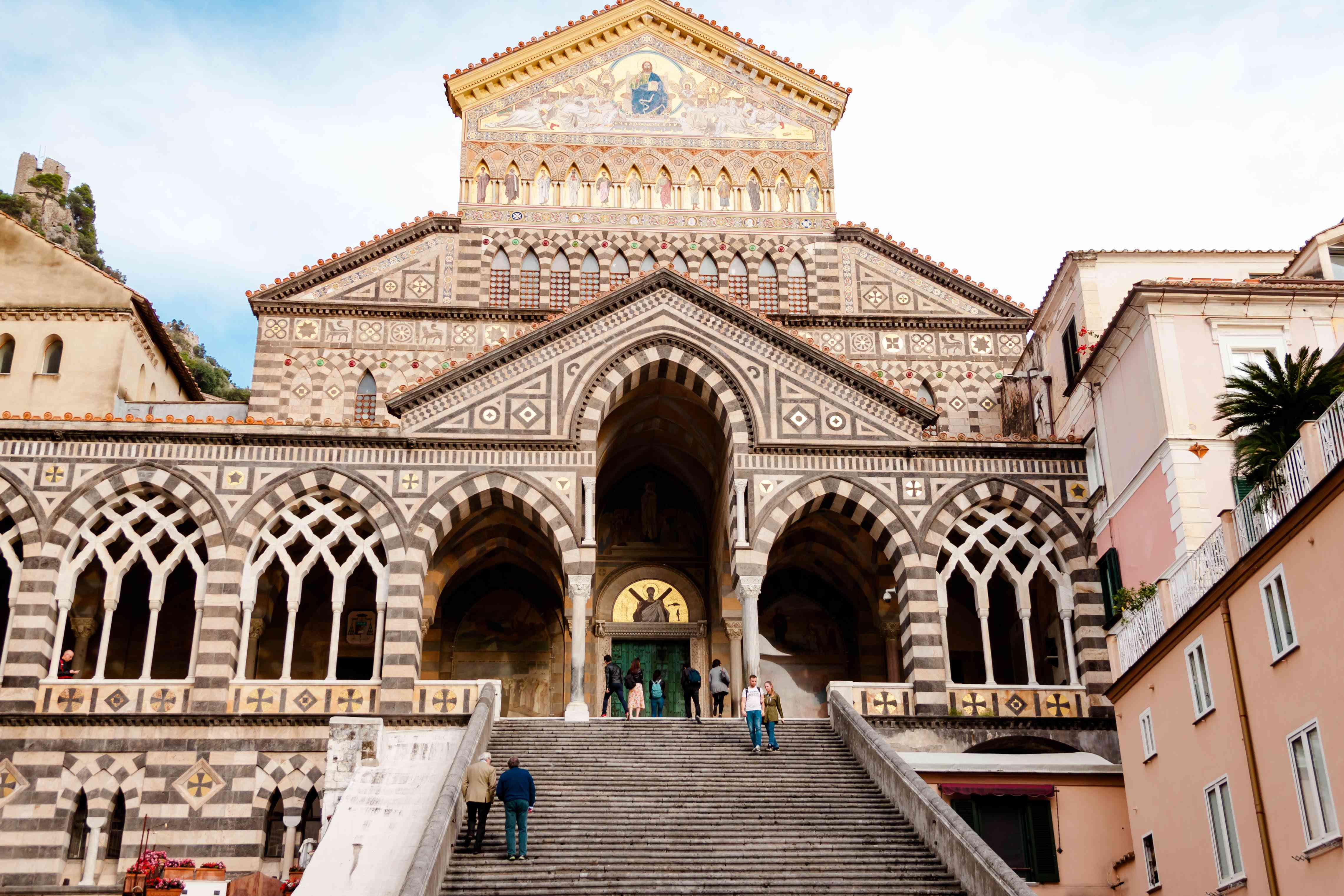 Italian Amalfi Cathedral duomo di Sant'andrea Church of St. Andrew front view. People watch the temple from below on the steps and are going to ascend
