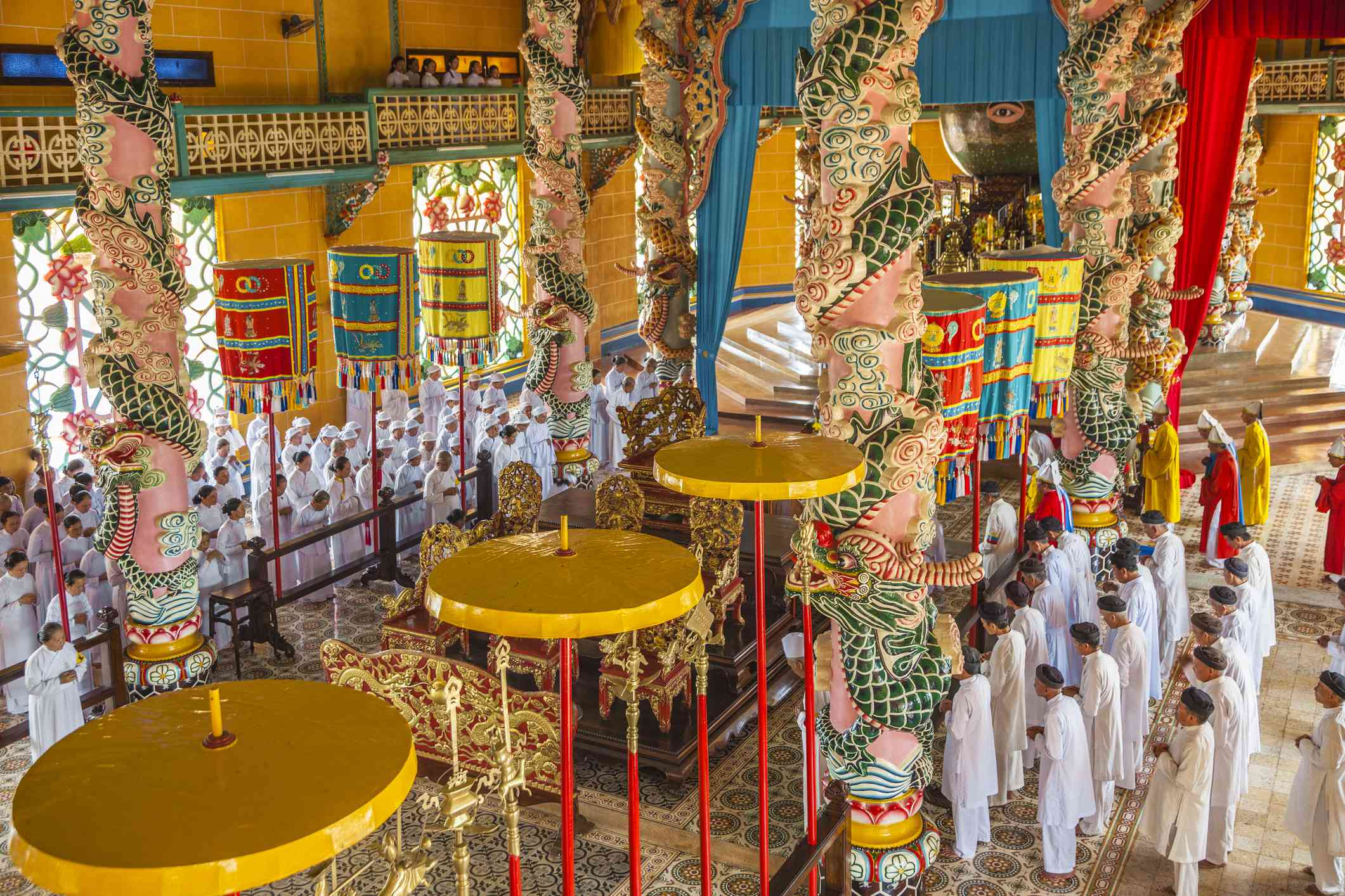 people dressed in while prageing inside an ornately decorated vietnamese temple