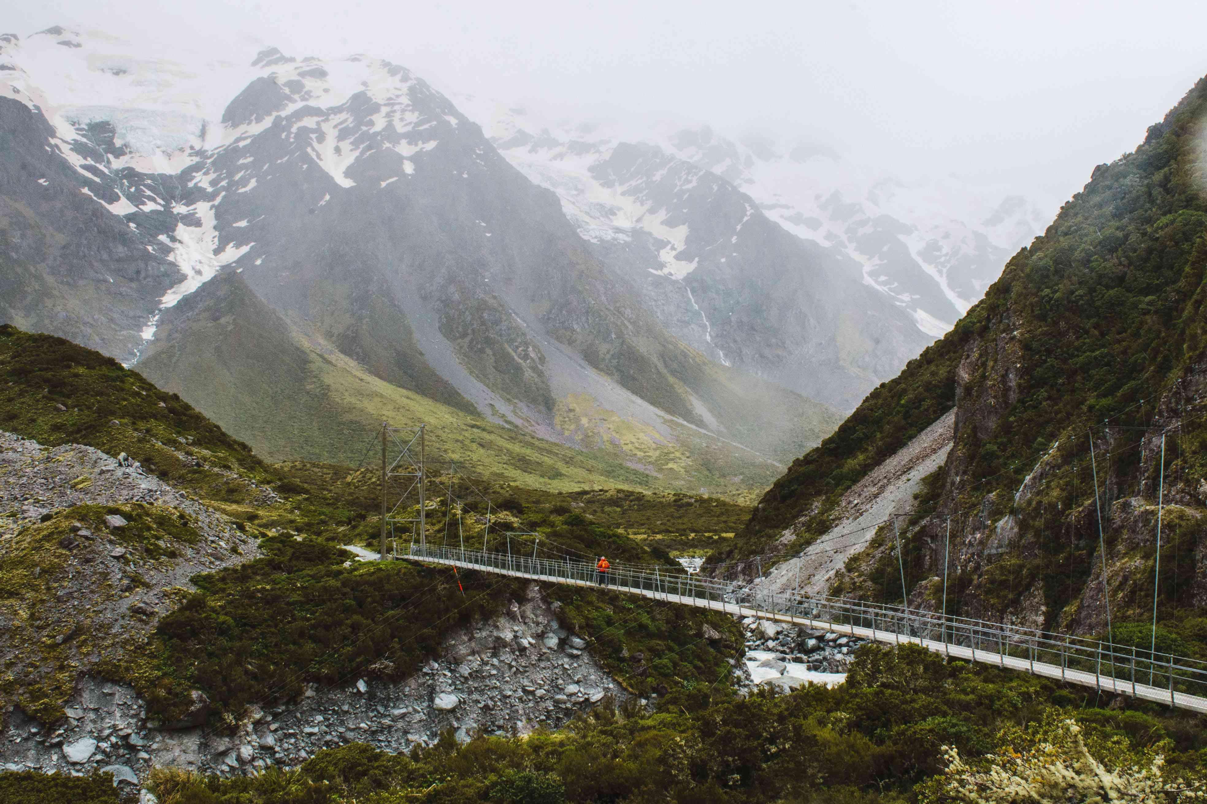 Una persona con una chaqueta roja cruzando un puente colgante en el Hooker Valley Trail
