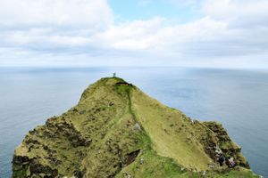 Two hikers standing on a remote mountain on the Faroe Islands