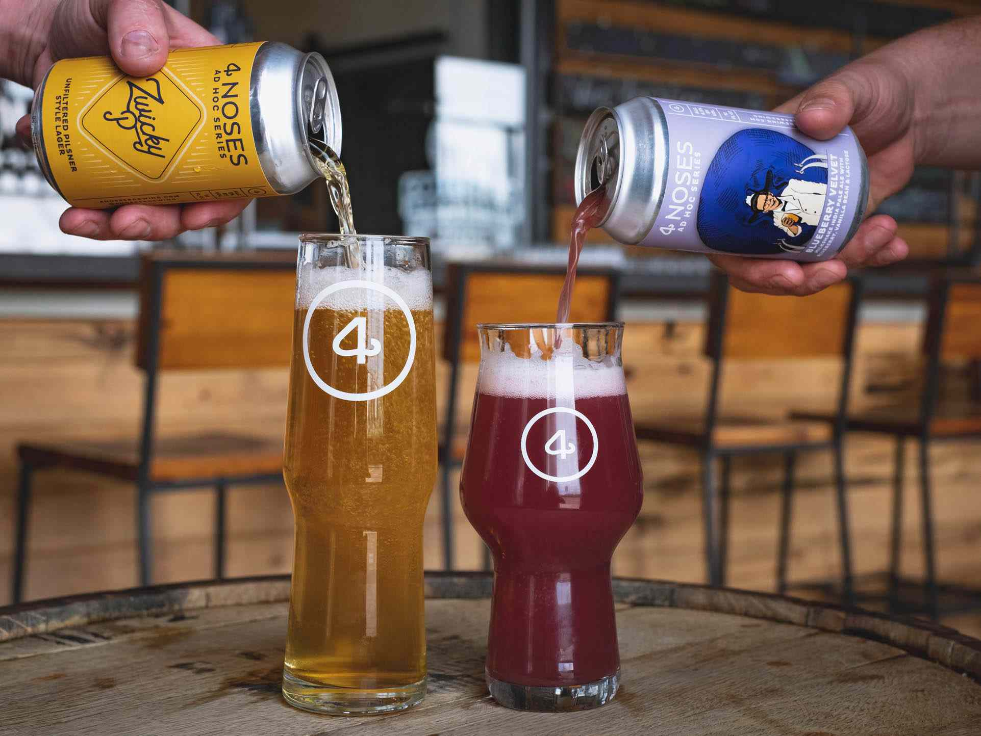 Two people pouring different beer from 2 different 4noses cans into 4noses branded pint glasses