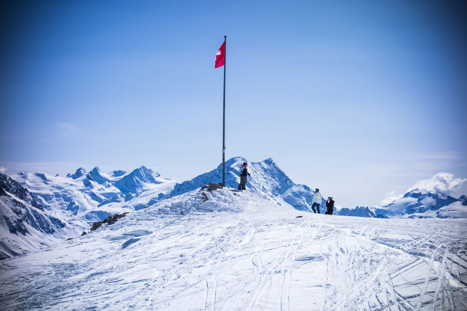 Three tourists and Swiss flag in snow covered mountains, Sankt Moritz, Engadin, Switzerland