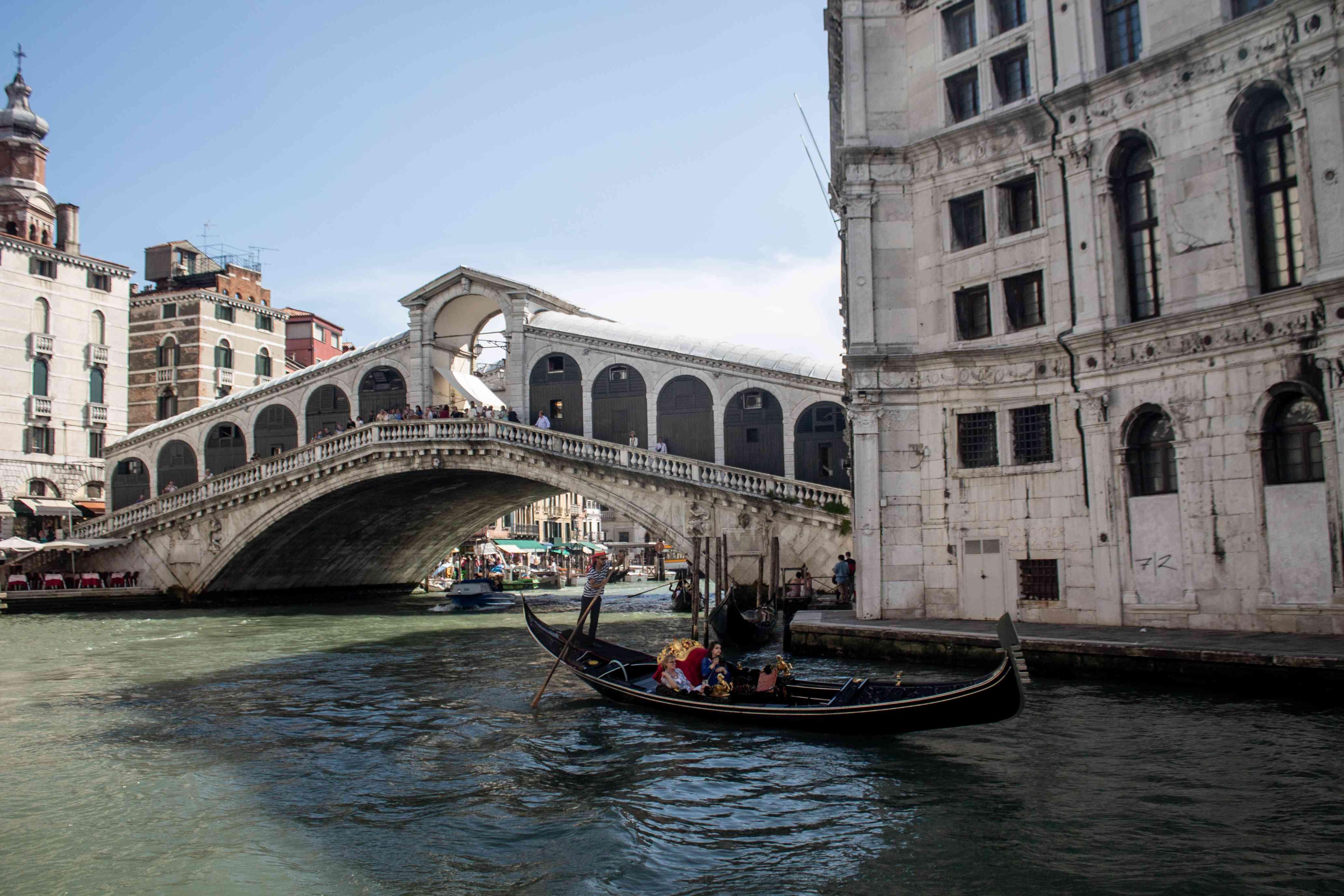 A gondola going by Rialto Bridge