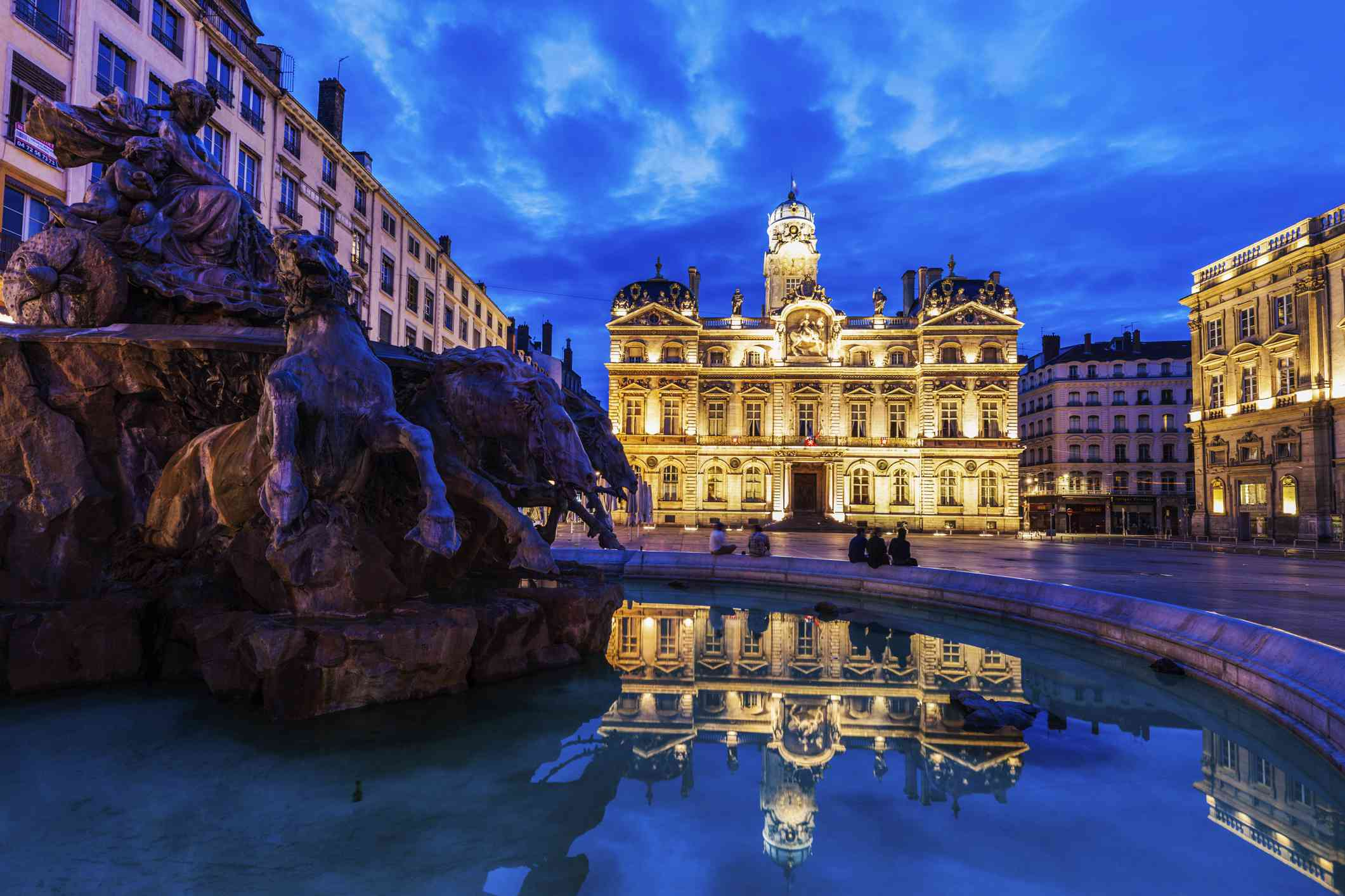 Lyon City Hall on Place des Terreaux and Bartholdi Fountain at night.