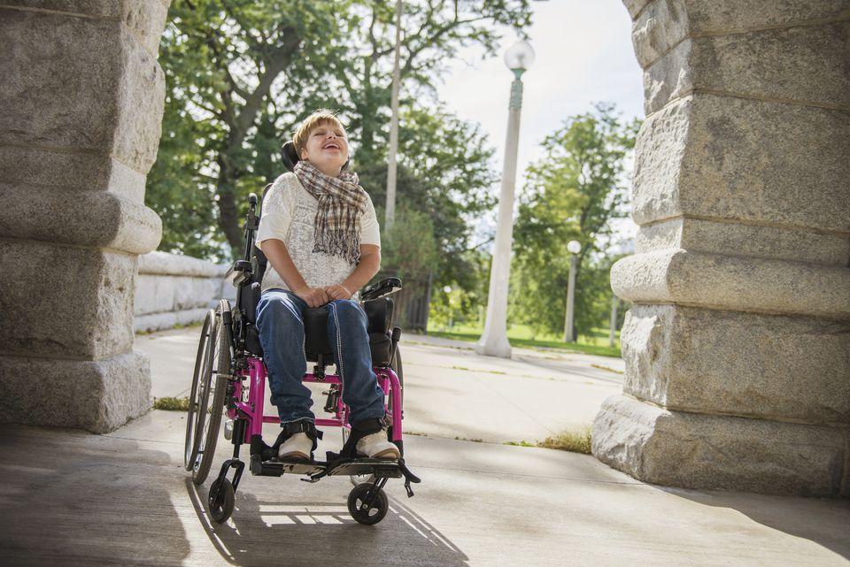 Mujer parapléjica en silla de ruedas bajo arco de piedra