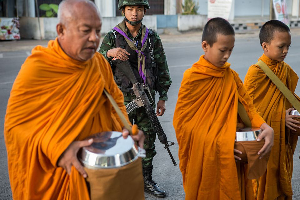 Armed soldiers protect Buddhist monks on their morning rounds in Pattani, Thailand
