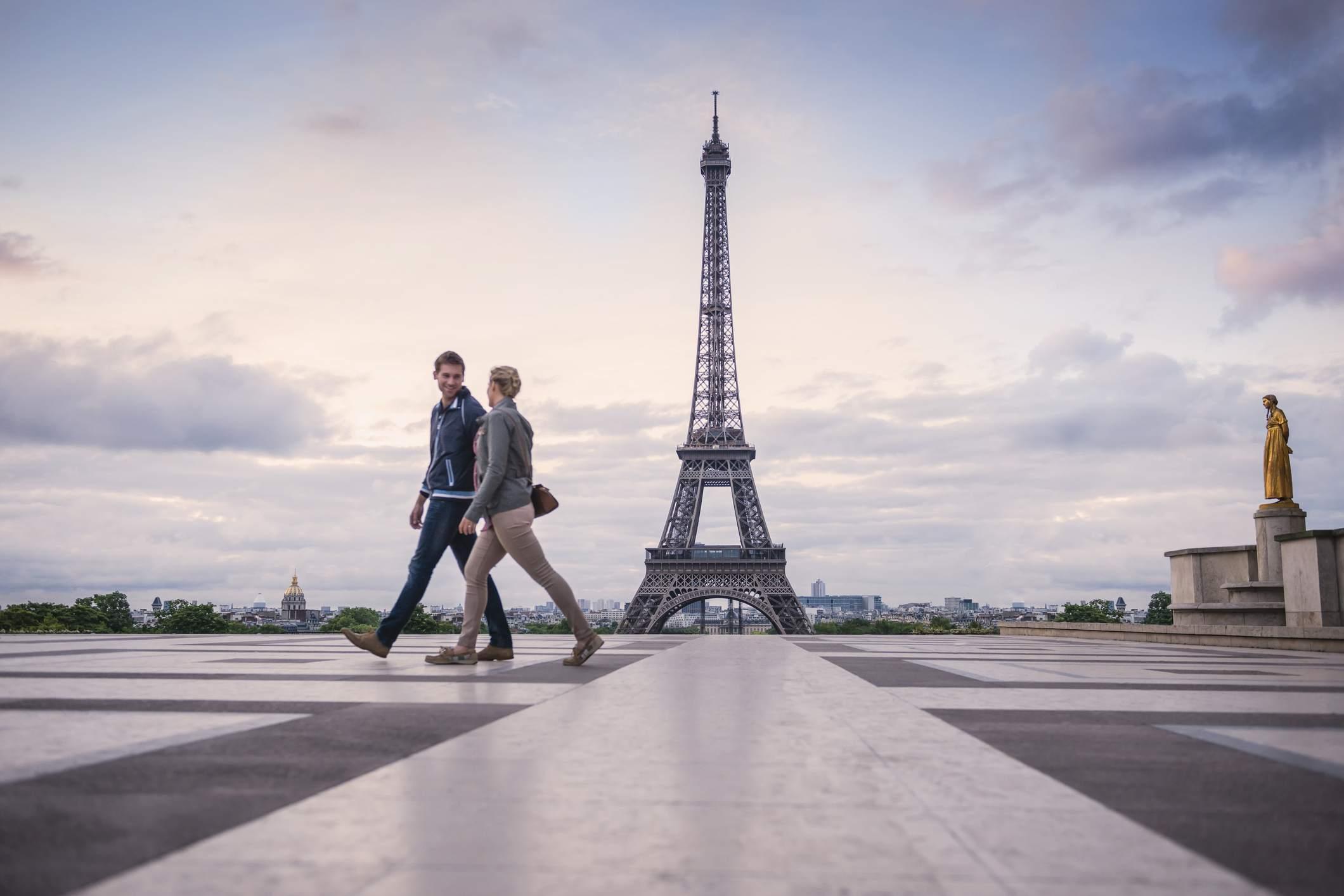 Caucasian couple walking near Eiffel Tower, Paris, France