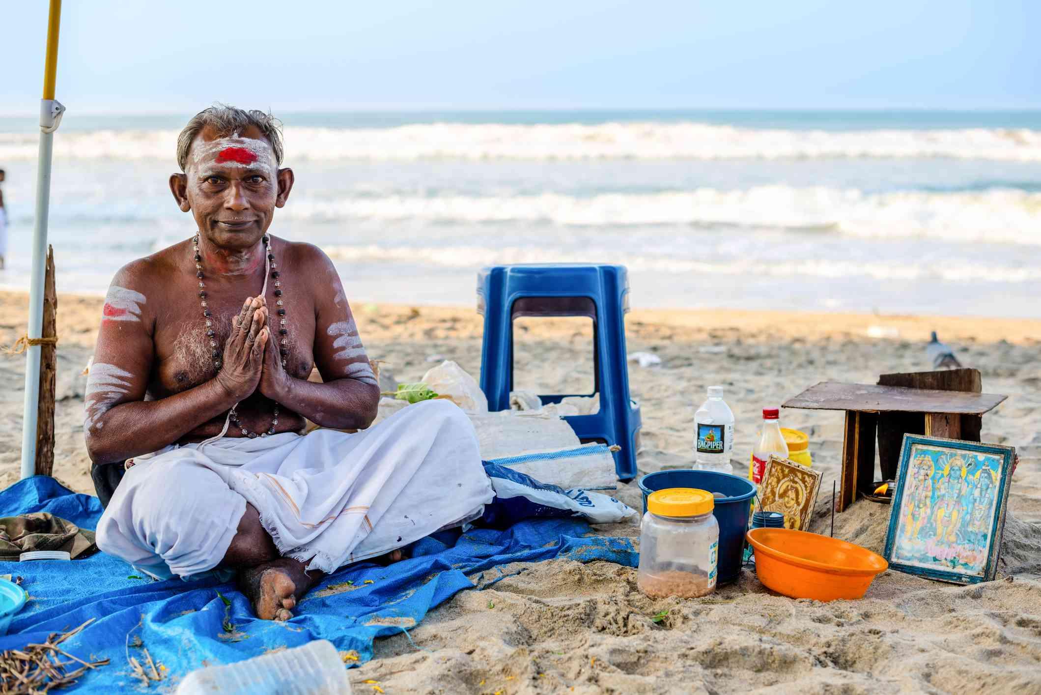 Brahmán hindú con atributos religiosos se sienta en Namaste mudra en la playa de Varkala, Kerala