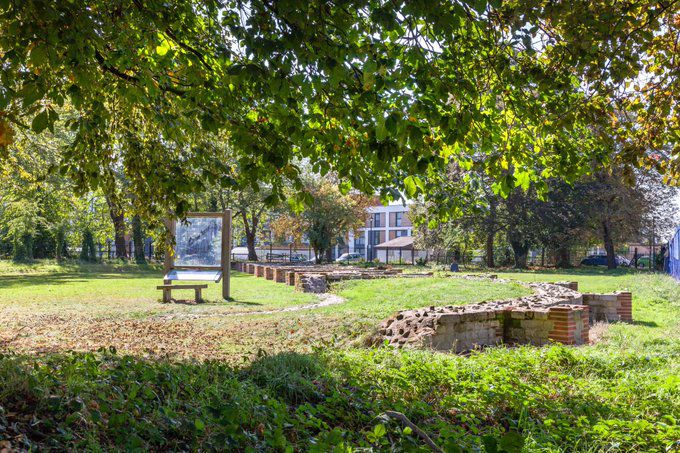 Ruins of roman circus in colchester with the branches of a tree in the foreground
